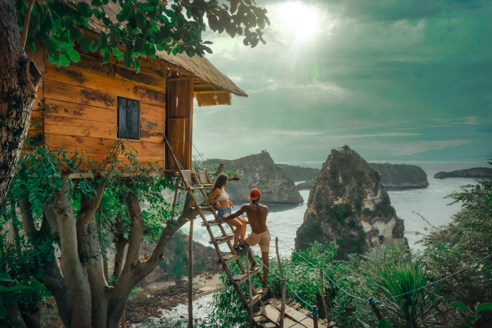 A young couple stands on the steps to their amazing tree house and look out at the ocean with gigantic rocks. The sun setting is peaking through the clouds.
