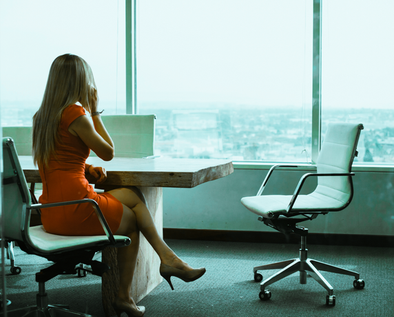 A female business owner makes a phone call in a board room to discuss what the marketing strategy should be. The room is nice and it looks out over the city. The woman is wearing a red dress.