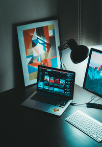 A creative working space for a digital marketing team has dim lighting and abstract painting on the table with a laptop and iMac computer