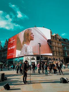 Beautiful blonde woman on a large digital billboard with red background above people walking in the streets while a man plays guitar.