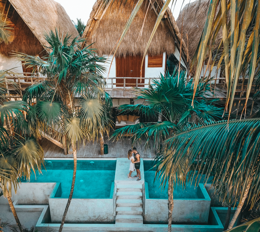 Couple stands and kisses by the pool of a beautiful hotel with palm trees as the sun is setting.
