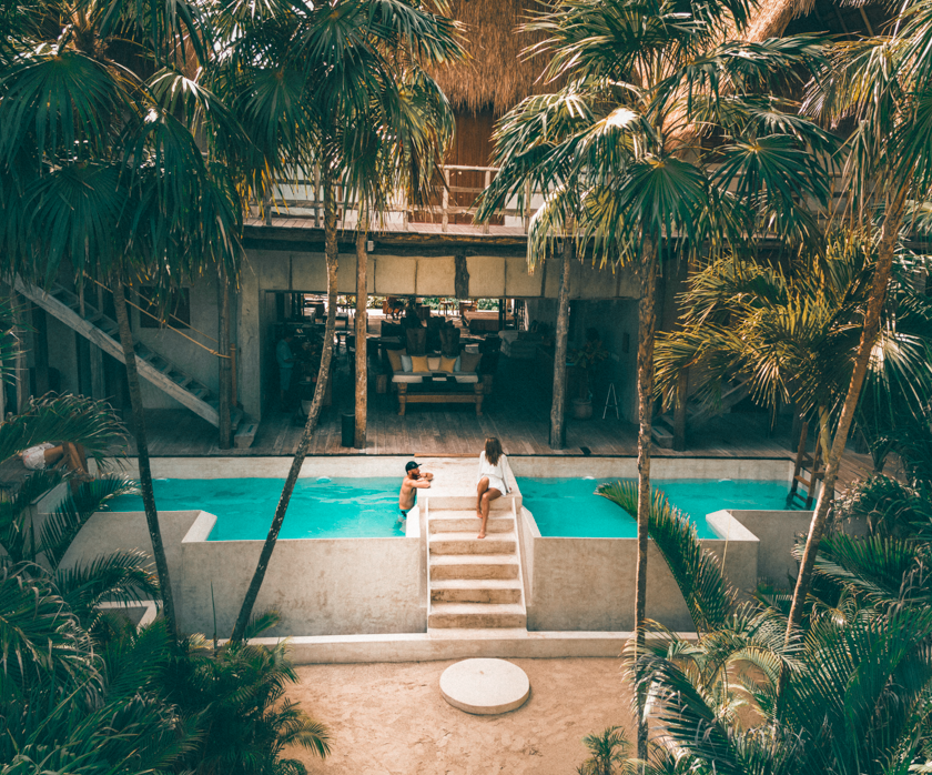 A young couple enjoys each other's company on their anniversary getaway by the pool at their favorite hotel. Palm trees, blue water, and amazing, private rooms make this hotel a dream.