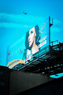 Large blue billboard with beautiful model with brown hair and the sky is blue behind the billboard