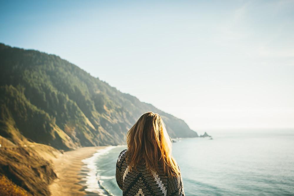 Una mujer soltera se para y mira el océano mientras reza.