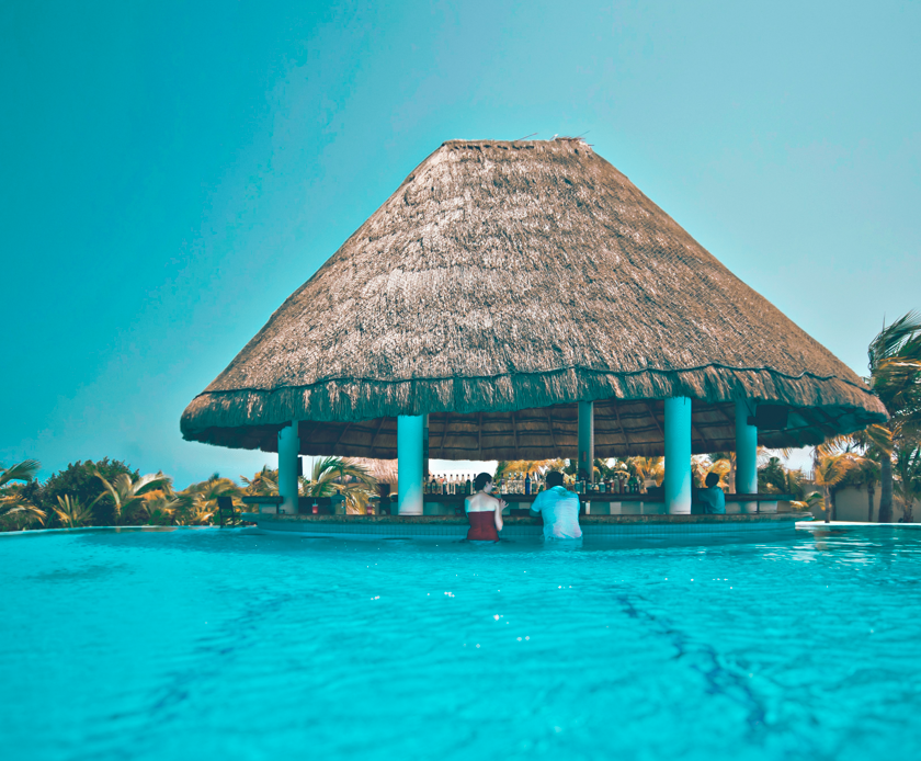 A retired couple stands in pool and leans over the edge to talk to one another in the mid day as a tiki hut provides shade.