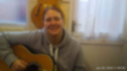 Charlotte chilling out playing her acoustic guitar.