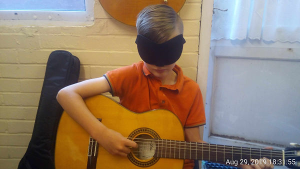 Tom practising his chord changes on his guitar while wearing a blind fold.