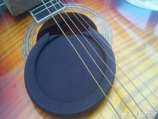 Fitting a squeal buster to a student's acuostic guitar to stop feedback occuring.