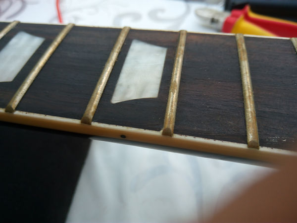 Cleaning the frets on your guitar.