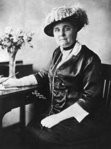 American social worker and suffragist Jane Addams (1860 - 1935) wearing a hat and gloves while seated at a writing desk with a pen in hand.   (Photo by Hulton Archive/Getty Images)