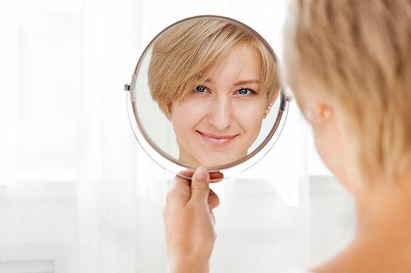 woman looking in mirror. dermal fillers benefit, dermal filler advantages, why use dermal fillers, hyaluronic acid injections, anti-wrinkle skin treatment, skin plumping