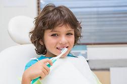 child in dentist chair brushing teeth
