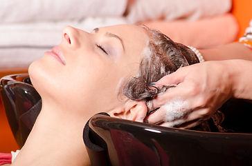 Girl washing hair in hairdressing salon.