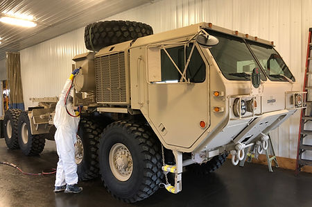 Carwell application being sprayed on a military HEMTT vehicle
