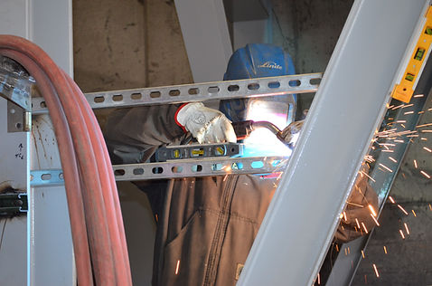 A QPC welder works on constructing their paintline