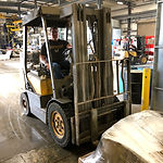 Materal handler moving a pallet of parts with a fork-lift
