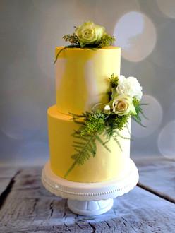Gele bruidstaart met verse bloemen