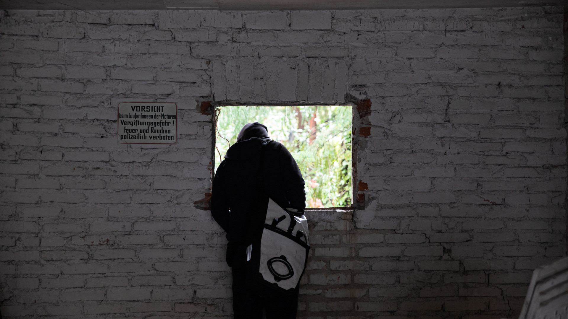 An activist looks through the back of the garage window into the backyard in a squatted house.