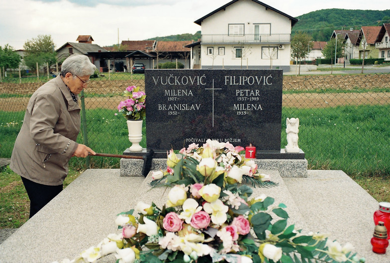 Milena cleans her husband's grave