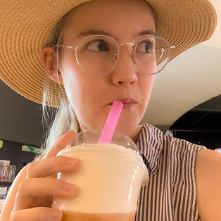 A selfie of Kat Fenton trying a sip of cheese tea