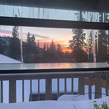 Icicles hang from the window a the sun rises behind snow covered evergreens