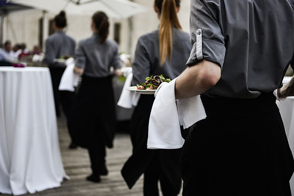 Waiter carrying plates with meat dish on