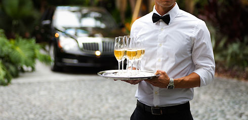 Black tie waiter serving champagne outdo