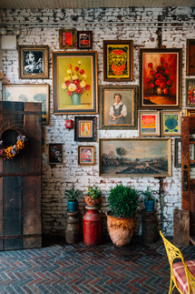 South House Bar and Restaurant with a collage of paintings on white-washed brick wall