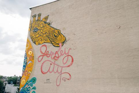 Giraffe mural on Jersey City building by artist Catherine Hart