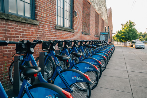 Row of Citibikes docked on a Jersey City sidewalk near 380 Newark Ave