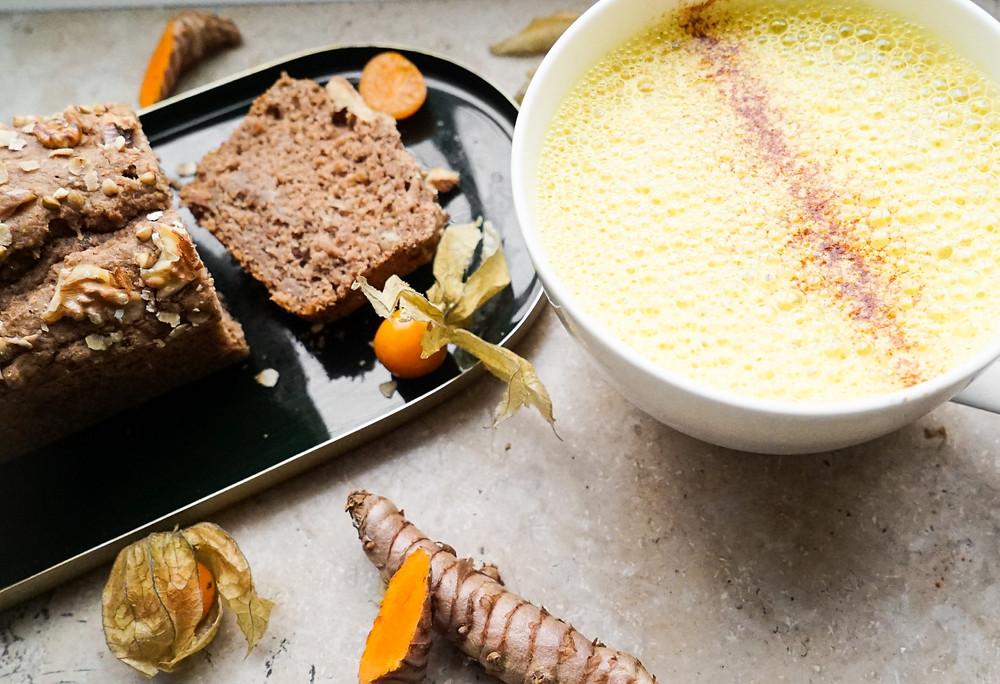 selbstgemachte Goldene Milch, Kurkuma-Latte oder Tumeric-Latte mit selbstgemachtem Bananenbrot