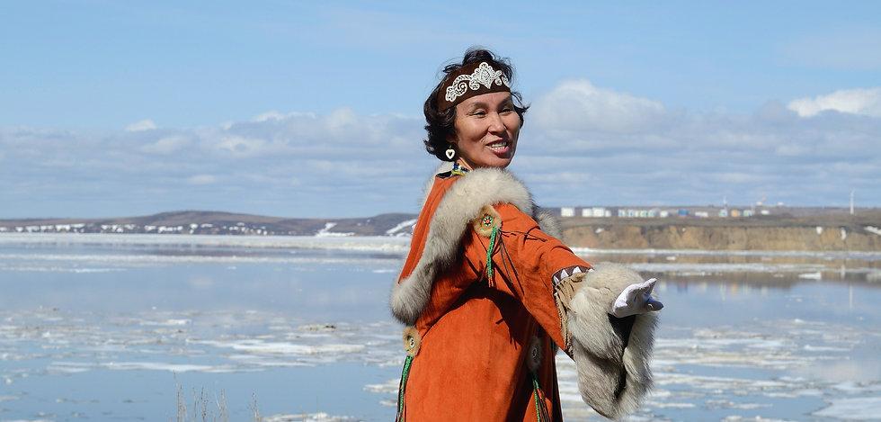 Indigenous woman in orange dress.