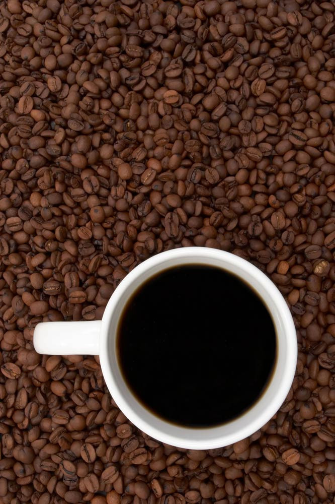 Cup of coffee with a background of coffee beans