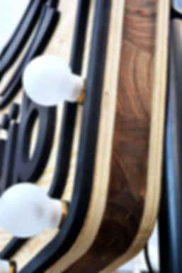 Détaille de l'enseigne sur mesure en bois et sa lumière retro Us. Parle Studio AA , créateur d'identité et moyens de communications innovants.