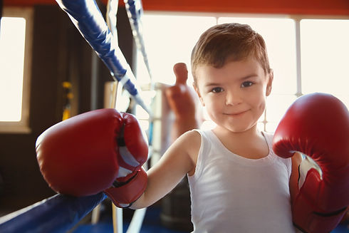 Little boy in boxing gloves on ring.jpg