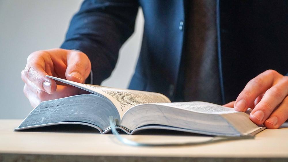 Mann im Anzug liest in Bibel, Großaufnahme