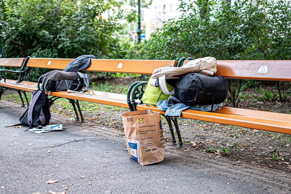 Zwei Bänke, mit einem Schlafsack, Decken und einer Tasche aus Karton