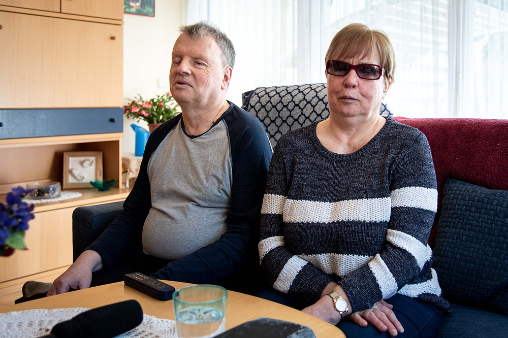 Bruno und Petra sitzen auf ihrer Couch im Wohnzimmer.