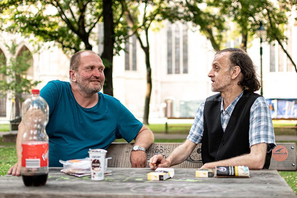 Dieter und Christian sitzen auf einer Park im Votivbank. Die beiden trinken, essen und reden.
