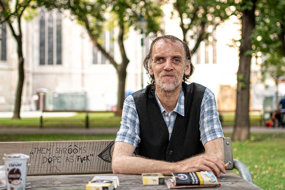 Dieter sitzt auf einer Bank im Votivpark. Vor ihm liegen Zigaretten und ein Eiskaffee.