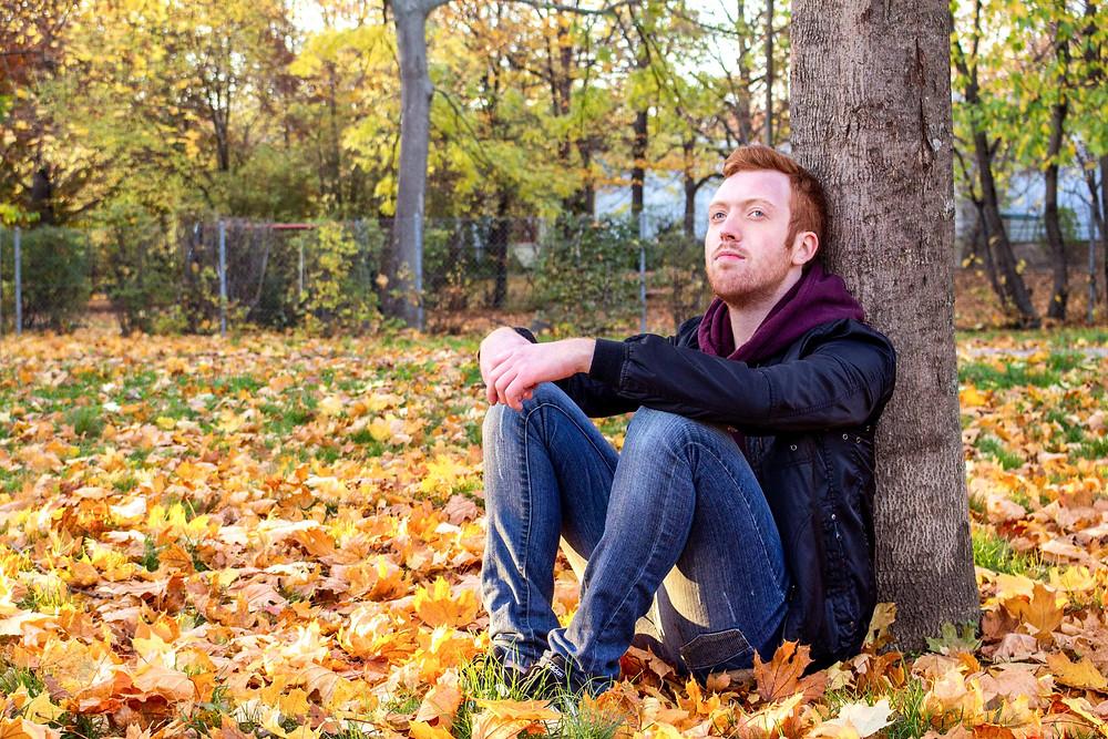 Mann lehnt an Baum und schaut in die Ferne