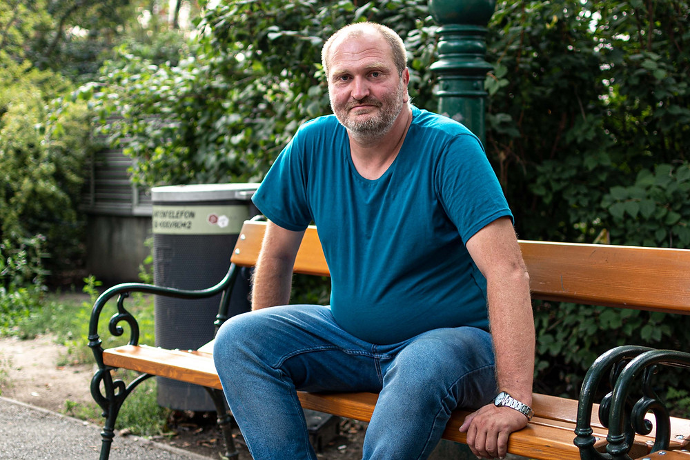 Christin sitzt auf einer Bank im Votivpark. Auf dieser Bank schläft er auch.