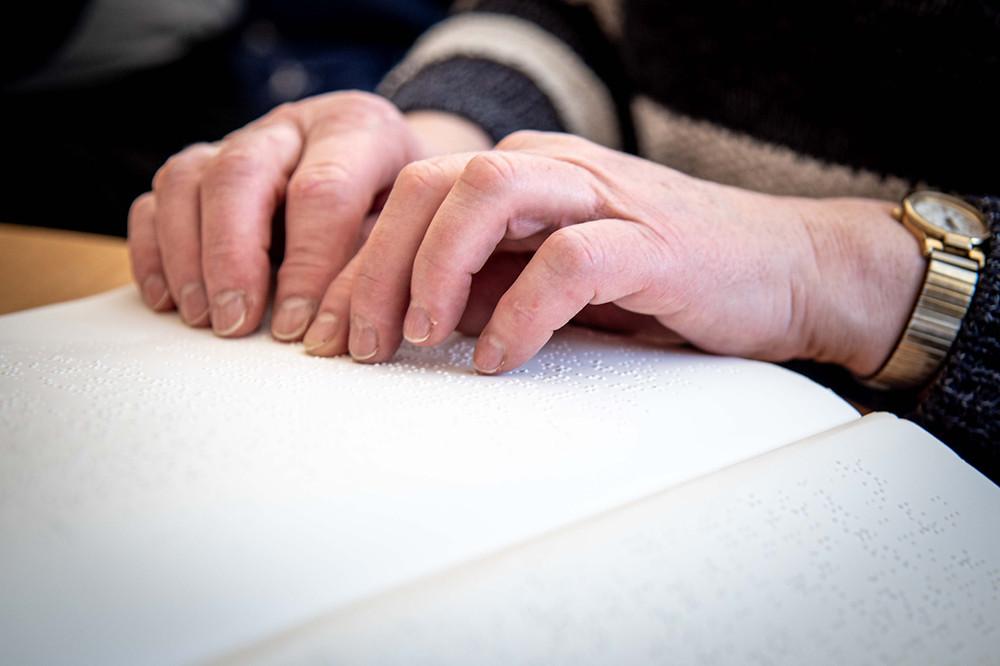 Petra hat ihre Hände auf einem Buch, das in Blindenschrift gedruckt ist
