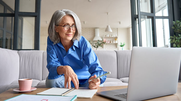 Senior mature older senior adult professional business woman working on laptop from home o
