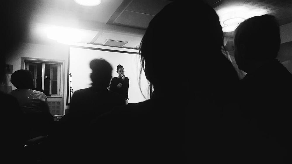 Syntolkning: Wendy Francis uppträder på scen. Svartvit bild, siluetten från publiken.