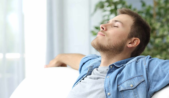 Man on couch taking deep breath