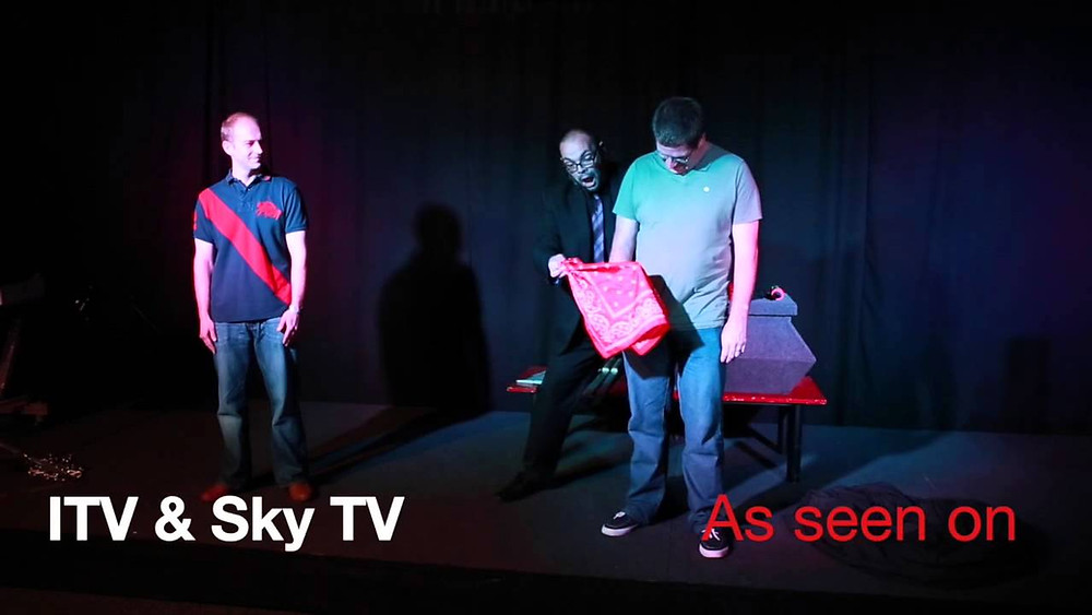 a magician and two assistants on stage performing magic using a red balaclava