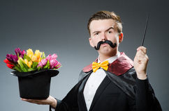 magician with a moustache holding a wand and hat with flowers blossoming