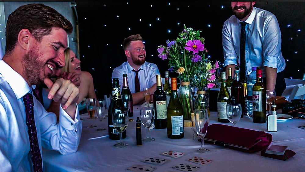 magician making men smile and laugh around a table at a party