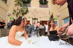 Magician performs close up magic trick around a table at a wedding that leaves guy face palming
